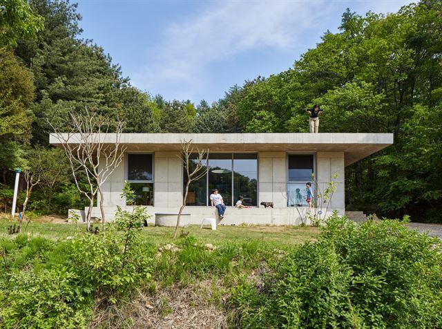 경기 광주시 도척면에 위치한 에이리 하우스가 푸른 숲을 배경으로 나지막하게 들어서있다. 회색의 노출 콘크리트를 사용한 검박한 집은 장식을 배제해 완성되지 않은 듯한 느낌을 준다. ©노경 건축사진작가