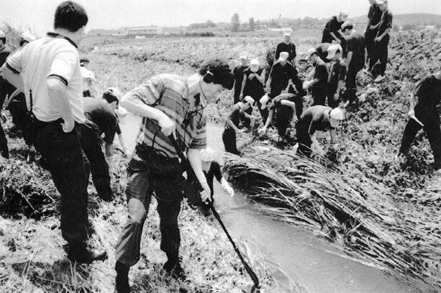 1993년 7월 화성연쇄살인사건 수사본부 경찰들이 화성군 정남면 관항리 인근 농수로에서 유류품을 찾고 있는 있다. 연합뉴스