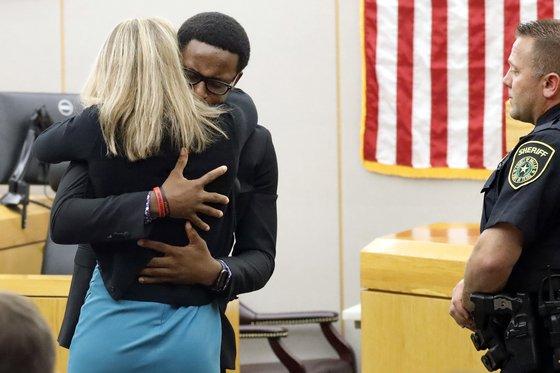 2일(현지시간) 미국 텍사스주 댈러스 지방법원에서 실수로 자신의 형을 총격해 죽인 전직 여성 경찰관 앰버 가이거(왼쪽)와 '용서의 포옹'을 하고 있는 브랜트 진. [로이터=연합뉴스]