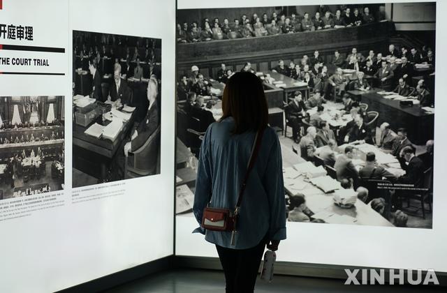 【난징(중국)= AP/뉴시스】 지난 9월 18일 난징에서 열린 난징대학살 71주기 기록사진 전시회에서 한 관람객이 전쟁후의 도쿄 일본군 전범 재판에 관한 사진을 들여다 보고 있다.  이 전시회는 2020년 3월까지 계속된다.