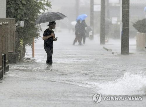 태풍 하기비스 영향으로 물에 잠긴 일본 도로 (시즈오카 교도=연합뉴스) 12일 제19호 태풍 하기비스의 영향으로 폭우가 쏟아진 일본 시즈오카(靜岡)시의 도로가 물에 잠긴 가운데 행인이 걸어가고 있다. 2019.10.12 bkkim@yna.co.kr