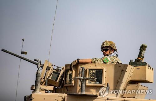 여성 쿠르드 민병대 '여성수비대'(YPJ)의 휘장을 어깨에 달고 철수하는 병사 [AFP=연합뉴스]