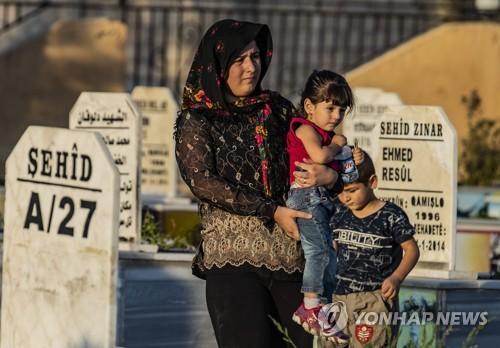이달 14일 시리아 북부 라스알아인의 묘지를 찾은 쿠르드 주민 [AFP=연합뉴스]