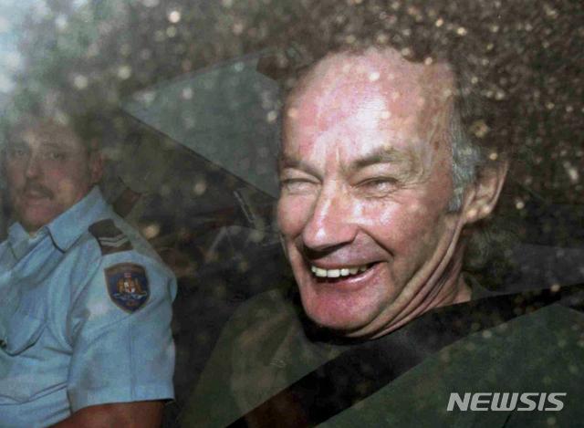 【시드니(호주)= AP/뉴시스】 20대 젊은 배낭족 여행자들을 차에 태워준 뒤 살인범으로 돌변해 벌판에서 차로 추격하며 사냥했던 희대의 연쇄살인범 아이반 빌랏이 1997년 11월 4일 재판정으로 호송되면서 웃어대고 있다. 그는 종신형의 7배 금고형을 선고받았으나 27일(현지시간) 교도소내 병동에서 식도암과 위암으로 숨졌다.