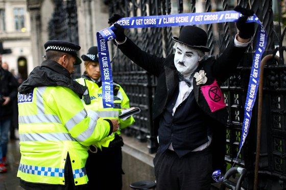 찰리 채플린으로 분장한 시위대가 영국 의회 밖에서 시위 중 체포되고 있다. [로이터=연합뉴스]