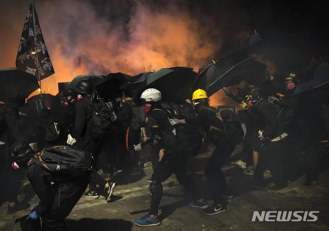 【홍콩=AP/뉴시스】홍콩 반정부 민주화 시위에 참가한 학생들이 13일 새벽 홍콩 중문대학에서 우산을 방패 삼으며 경찰과 대치하고 있다. 전날엔 경찰이 대학 캠퍼스 안까지 진입해 최루탄을 발사하기도 했다. 2019.11.13