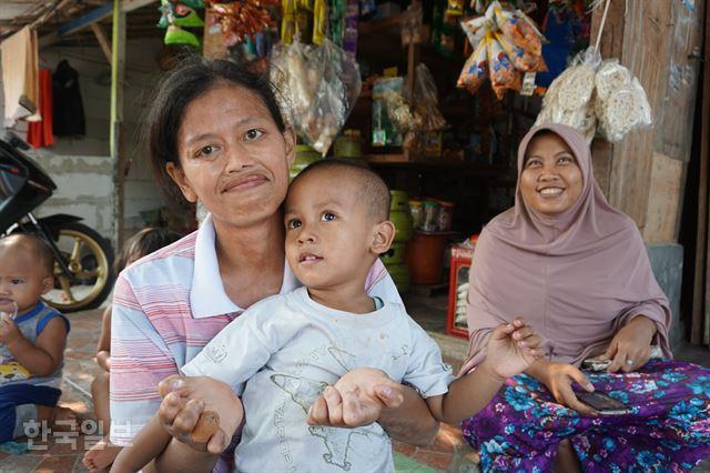 시타날라 마을의 한센인 데위씨가 세 살배기 아들과 함께 웃고 있다.