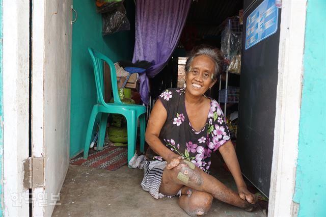 두 발과 손가락이 모두 없는 티틴씨가 시타날라 마을 자신의 집에서 동네 공부방 컴퓨터 교사로 일하는 아들 자랑을 하고 있다.