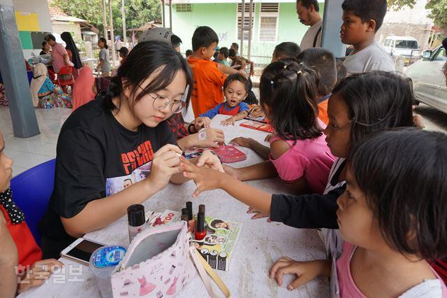 최영미씨 딸 김예빈양이 시타날라 마을회관 마당에서 한센인 자녀들의 손톱을 칠해주고 있다.