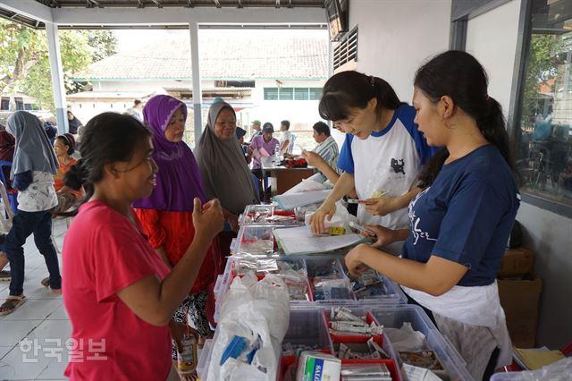 인도네시아 반텐주 탕에랑의 한센인 집단촌 시타날라 마을에서 봉사자들이 한센인들에게 약을 나눠주고 있다.