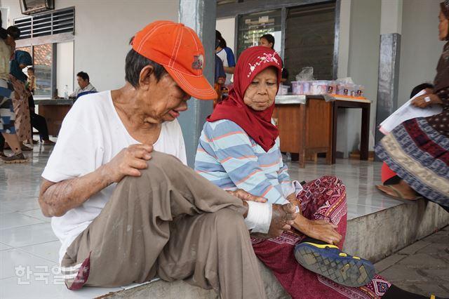 인도네시아 반텐주 탕에랑에 있는 한센인 마을 시타날라의 마을회관 마당에서 한 한센인이 진료를 받기 전 자신의 상태를 살펴보고 있다.