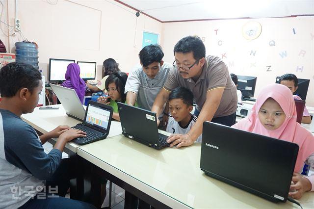 인도네시아 반텐주 탕에랑에 있는 한센인 집단촌 시타날라 마을의 공부방에서 에르윈씨와 김동식씨가 컴퓨터 조작에 애를 먹는 한 학생을 돕고 있다.