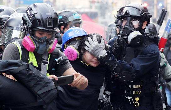 지난 18일(현지시간) 오후 홍콩 이공대에서 경찰이 시위대를 연행하고 있다 (사진=뉴시스)