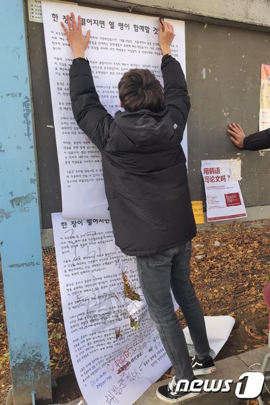 19일 세종대 학생이 훼손된 대자보 위에 새 대자보를 붙이고 있다 © 뉴스1