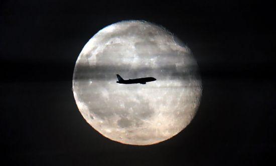 보름달 앞을 비행 중인 여객기. 달의 하루는 29.5일입니다. [사진=EPA/연합뉴스]