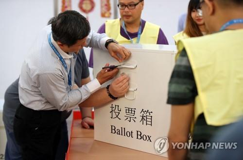 투표함 개봉하는 관계자 (홍콩=연합뉴스) 김인철 기자 = 홍콩 구의원 선거일인 24일 오후 홍콩 구룡공원 수영장에 마련된 투표소에서 관계자들이 개표작업을 위해 투표함을 개봉하고 있다. 2019.11.25 yatoya@yna.co.kr