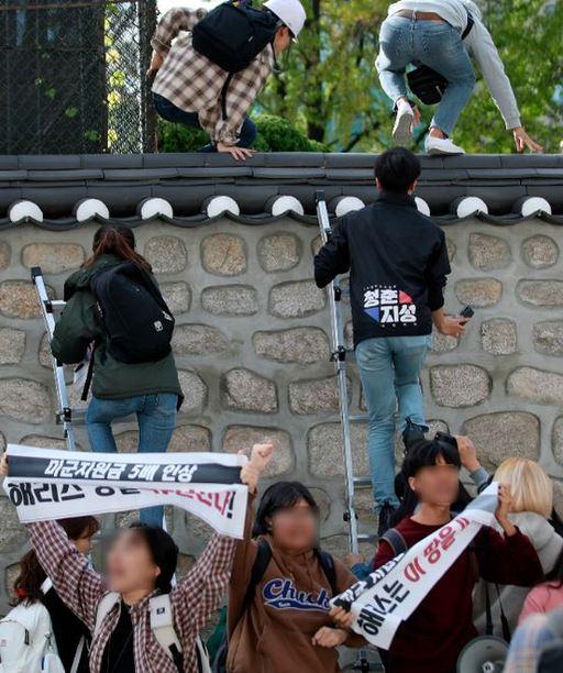 한국대학생진보연합이 10월 18일 오후 서울 중구 주한 미국대사관저에서 방위비분담금 협상 관련 기습 농성을 하기 위해 담벼락을 넘고 있다. 뉴시스