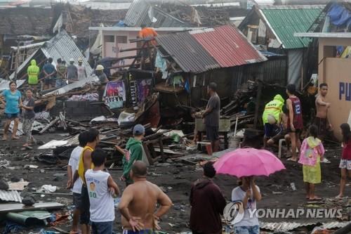 태풍 '간무리' 지나간 필리핀 레가스피 (레가스피 로이터=연합뉴스) 2일(현지시간) 태풍 '간무리'가 지나간 필리핀 레가스피에서 주민들이 파괴된 주택 잔해 속에 서 있다. ucham1789@yna.co.kr