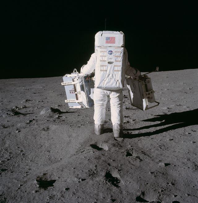 1969년 아폴로 11호에서 내린 조종사 버즈 올드린이 실험 장비를 들고 월면토로 덮인 달 표면을 걷고 있다. 미국 항공우주국(NASA) 제공