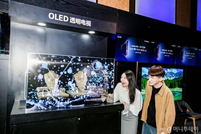 지난 9월 중국 베이징에서 열린 OLED 빅뱅 미디어 데이 행사에서 참석자들이 LG디스플레이의 55인치 투명 OLED 디스플레이를 관람하고 있다/사진제공= LG디스플레이