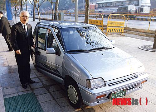 【서울=뉴시스】김우중 전 대우그룹 회장이 대우자동차 티코 앞에서 포즈를 취하고 있다. 뉴시스DB