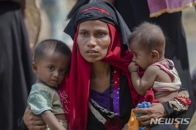 """[쿠투팔롱=AP/뉴시스] 로힝야 무슬림 주민들이 미얀마의 아웅산 수지 국가자문을 향해 """"우리의 증거를 바탕으로 세계가 판단할 것""""이라며 날선 반응을 쏟아냈다고 12일(현지시간) 가디언이 보도했다. 사진은 2017년 10월22일 세계 최대 규모의 난민촌인 방글라데시 쿠투팔롱에서 로힝야 무슬림 여성이 두 아이를 안고 있는 모습. 2019.12.12."""