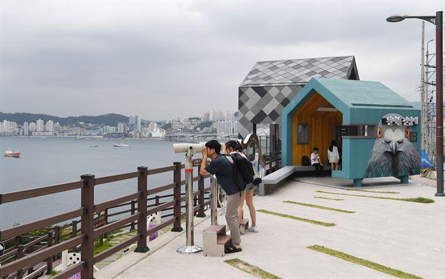 흰여울문화마을을 찾은 관광객들이 전망대에서 망원경으로 맞은편 송도를 비롯, 마을 앞 전경을 감상하고 있다.