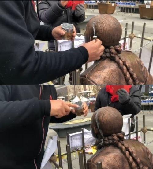 24일 머리 부분이 훼손된 전두환 동상을 접착제로 보수하고 있다. 5ㆍ18 구속부상자회 서울지부 제공
