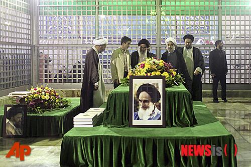 【테헤란=AP/뉴시스】하산 로하니 이란 대통령 당선인(오른쪽에서 3번째)이 16일(현지시간) 테헤란 외곽에 있는 '이슬람 혁명의 아버지' 아야톨라 호메이니의 사원을 방문에 그의 묘에서 기도하고 있다. 앞에 호메이니의 사진이 보인다. 로하니 당선인이 이날 이란 심각한 경제 문제는 하룻밤 만에 해결할 수 있는 문제가 아니라고 밝혔다.  2013.06.17