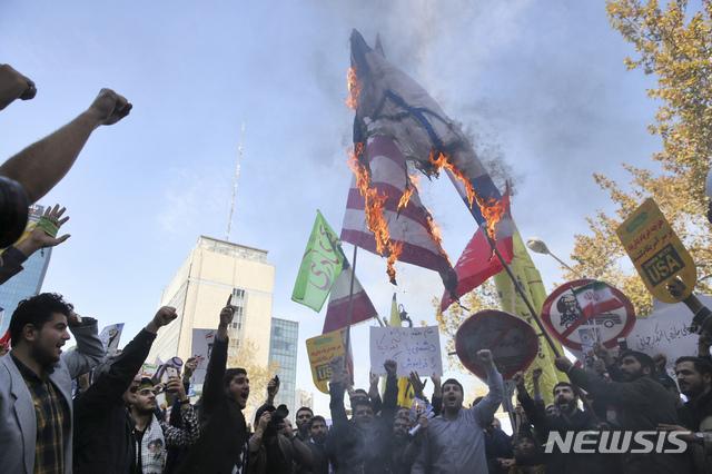 【테헤란=AP/뉴시스】이란 시민들이 지난 4일 테헤란에 위치한 이란 주재 전 미국대사관 건물 앞에서 미국과 이란의 국기를 태우며 시위를 벌이고 있다. 2018.11.5.