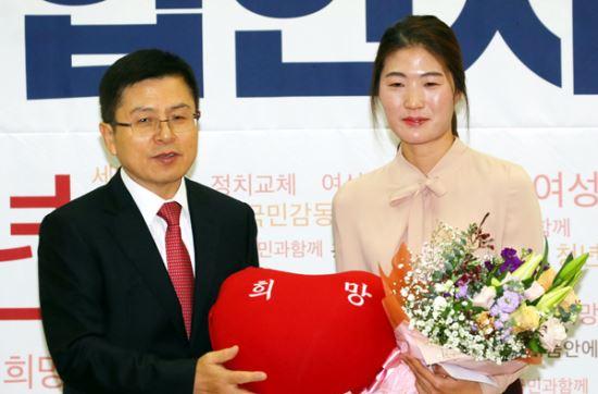 제21대 총선을 앞두고 자유한국당에 영입된 체육계 미투 1호인 김은희 씨가 8일 국회 의원회관에서 열린 한국당 영입인사 환영식에서 황교안 대표에게 당을 상징하는 빨간 쿠션을 건네받으며 기념촬영 하고 있다. 연합