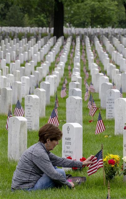 """미국에서 시신을 묻거나 태우는 대신 땅에 도움이 되는 방식으로 처리하는 '시신 퇴비화'가 5월부터 시행되는 가운데 한 여성이 버지니아주 알링턴 국립묘지에 안장된 남편의 묘비 옆에 앉아 있다. 미국에서는 남북전쟁 당시 전사한 군인의 시신을 보존하기 위해 방부 처리를 시작했는데, 환경론자들은 """"이 방식이 여러 가지 문제를 낳고 있다""""고 비판한다.UPI 연합뉴스"""