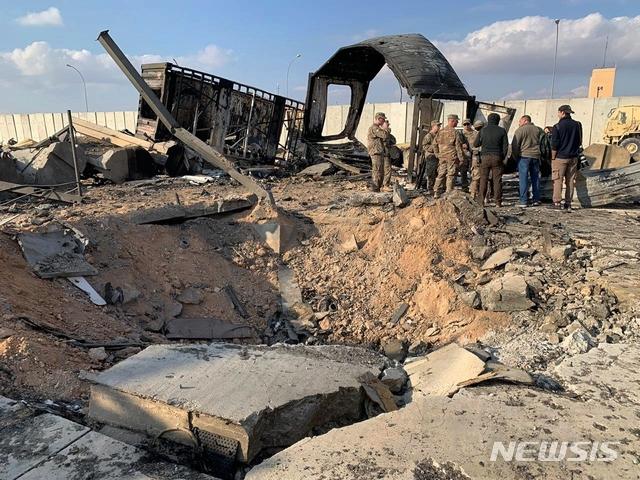 [아인알아사드=AP/뉴시스]미 군인들과 기자들이 13일(현지시간) 이라크 아인알아사드 공군기지에 남은 미사일 흔적 옆에 서 있다. 이 기지는 지난 8일 이란의 '가셈 솔레이마니 폭살' 보복공습을 받았다. 2020.01.14.