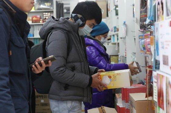 28일 서울 중구 명동의 약국에서 외국인 관광객이 마스크를 구매하고 있다. [연합뉴스]