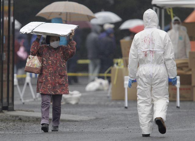 2011년 동일본 대지진으로 후쿠시마 원전 폭발 사고가 발생, 최악의 방사선 유출이 우려되는 일본 후쿠시마현 고리야마시 일대에서 마스크를 착용한 여성이 방사선 물질을 피하기 위해 머리 위에 보호구를 얹고 지나고 있다. 후쿠시마=AP연합뉴스