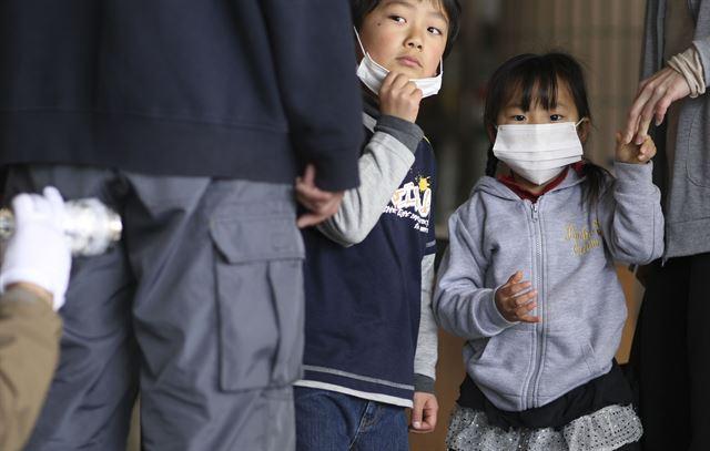 2011년 동일본 대지진으로 후쿠시마 원전 폭발 사고가 발생, 최악의 방사선 유출이 우려되는 일본 후쿠시마 청사에서 마스크를 쓴 일본 어린이들이 방사능 오염 검사를 받고 있는 어른들을 물끄러미 바라보고 있다. 후쿠시마=AP연합뉴스