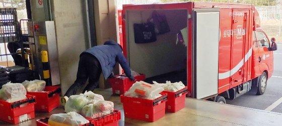 4일 롯데마트 직원이 김포 온라인전용센터에서 배송할 신선식품을 콜트체인시스템(냉장시스템)을 갖춘 차량에 싣고 있다. 롯데마트는 최근 신종 코로나 사태로 주문량이 급증하자 각 점포별 배송인력을 전원 가동하고 증차를 검토 중이다. [사진 롯데쇼핑]