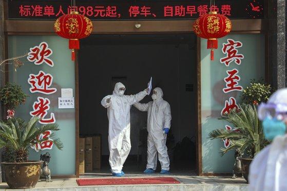 지난 3일 방호복을 입은 남성들이 중국 후베이성 우한시 당국이 격리포인트로 지정한 한 호텔을 나서고 있다. [AP=연합뉴스]