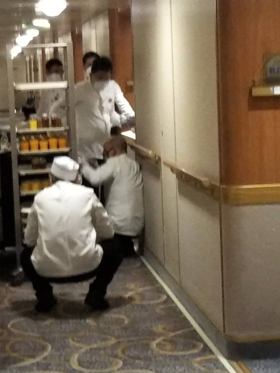 신종 코로나 감염증(코로나19)이 집단 발생한 다이아몬드 프린세스호의 승조원들이 비닐장갑과 마스크를 쓰고 객실에 음식을 배달하고 있다. [사진 일본인 승객 H씨]