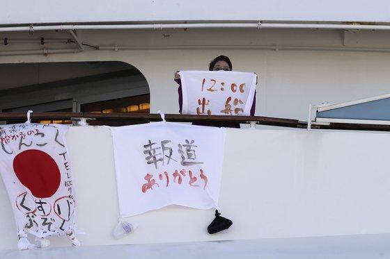 신종 코로나 감염증(코로나19)가 집단 발생한 다이아몬드 프린세스호의 한 여성 승객이 지난 11일 '12시에 출발한다'고 적힌 깃발을 들어보이고 있다. [AP=연합뉴스]