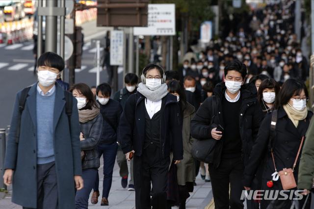 [도쿄=AP/뉴시스]20일 아침 일본 도쿄 추오구에서 시민들이 마스크를 쓴 채 출근하고 있다. 2020.02.20.