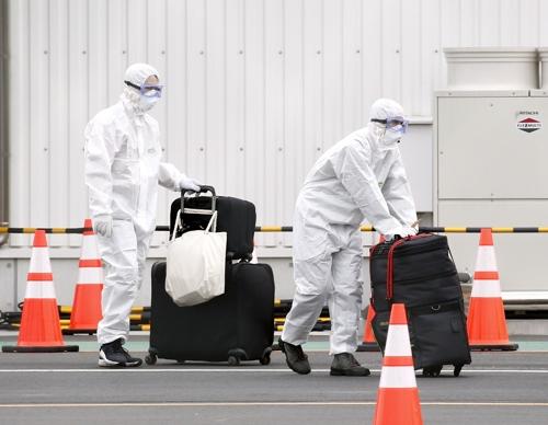 다이아몬드 프린세스 승객 짐 운반 (요코하마 교도=연합뉴스) 20일 오후 일본 요코하마(橫浜)항에서 방호복을 입은 작업자들이 크루즈선 다이아몬드 프린세스에서 내린 승객의 짐을 옮기고 있다. 이 배에서는 신종 코로나바이러스 감염증(코로나19) 환자가 수백명 확인됐다. 2020.2.20