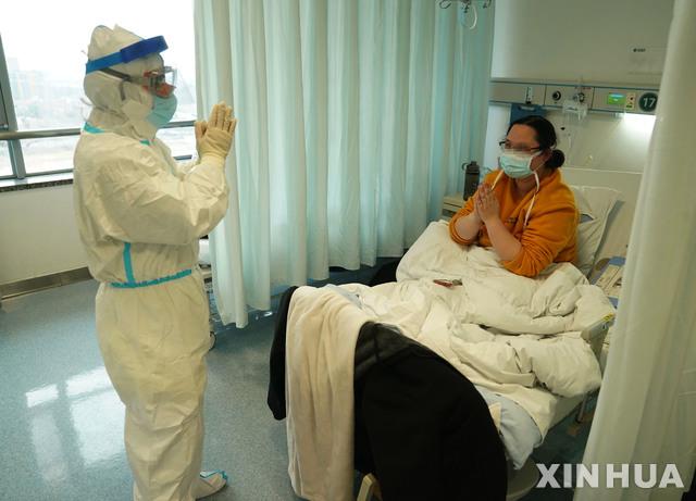[우한=신화/뉴시스]18일(현지시간) 중국 후베이성 우한의 한 병원에서 신종 코로나바이러스 감염증(코로나19) 치료를 받는 한 여성이 주치의인 자오젠핑 주임교수에게 고마움의 인사를 하고 있다. 이 여성은 코로나19 치료 중 아들을 출산했으며 태어난 아이는 의료진의 의학적 관찰을 받고 있다. 2020.02.19.