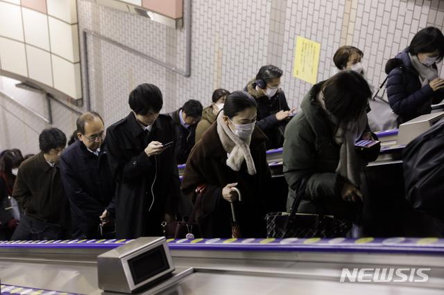 [도쿄=AP/뉴시스]28일 오전 일본 도쿄에서 사람들이 마스크를 쓴 채 출근하고 있다. 2020.01.28.