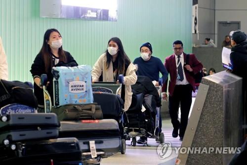 로스앤젤레스 국제공항에 마스크를 쓰고 입국하는 여행객들 [로이터=연합뉴스]