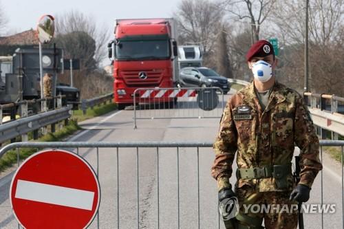 코로나19로 통제된 이탈리아 파도바 마을 (파도바 EPA=연합뉴스) 마스크를 쓴 이탈리아 군인이 24일(현지시간) 베네토 주 파도바 인근 마을 입구를 통제하고 있다.  ucham1789@yna.co.kr
