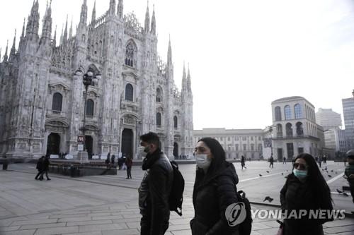 '코로나19 여파' 한산한 밀라노 두오모 성당 주변 (밀라노 AP=연합뉴스) 23일(현지시간) 이탈리아 북부 밀라노에서 신종 코로나바이러스 감염증(코로나19) 우려로 마스크를 착용한 사람들이 고딕 대성당인 '두오모' 앞을 지나가고 있다. leekm@yna.co.kr