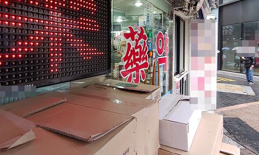 전국적으로 비가 내린 지난 28일 오전 서울 명동의 한 약국 앞에서 한 시민이 멀찍이서 유리문 넘어 내부를 들여다보고 있다.