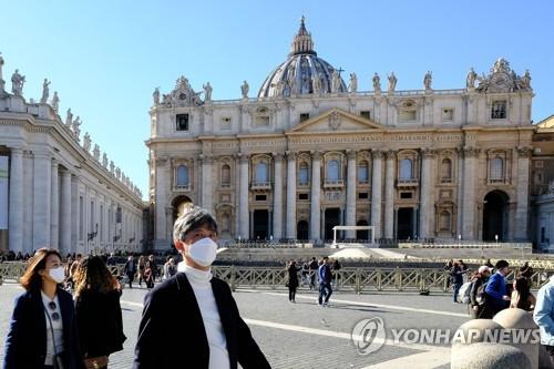 마스크를 쓰고 바티칸 성베드로 성당 앞을 지나는 관광객들. 2020.2.28. [AFP=연합뉴스]