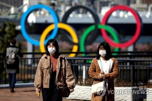 지난달 27일 도쿄에서 마스크를 쓴 채 오륜기 조형물 주변을 지나는 행인들 [로이터=연합뉴스]